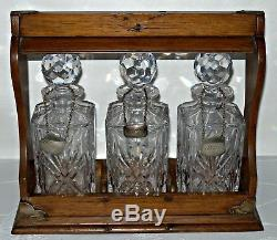 An Edwardian Oak Three Bottle Tantalus with 3 Metal Decanter Labels
