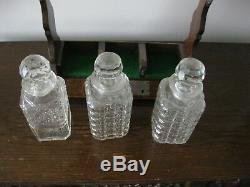 An antique Victorian oak three cut glass decanters tantalus with s/p mounts