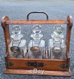 Antique Tiger Oak Tantalus With Original Cut Glass Decanters. Sherry Gin Scotch